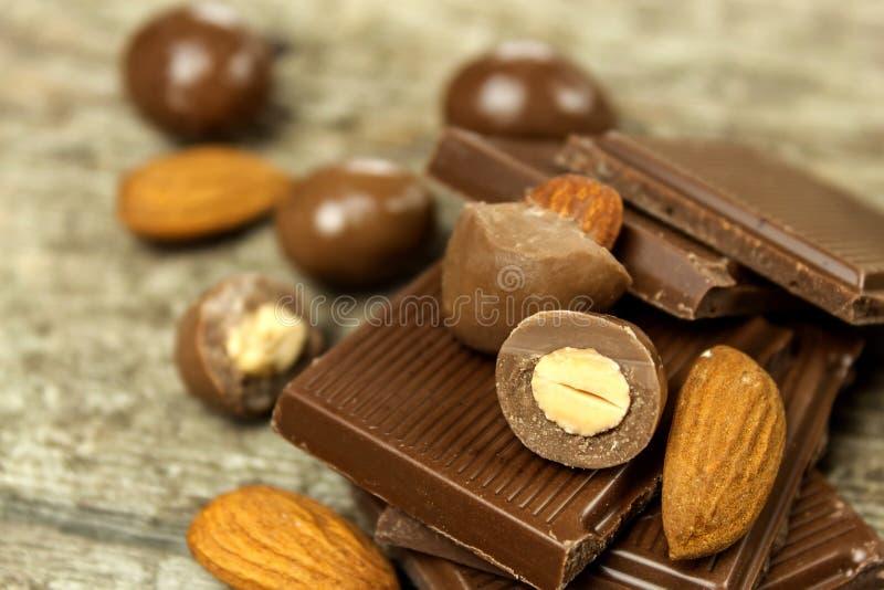 Almendras en esmalte del chocolate en una tabla de madera vieja Comida malsana Riesgo de obesidad y de diabetes Tuercas dulces Ch foto de archivo