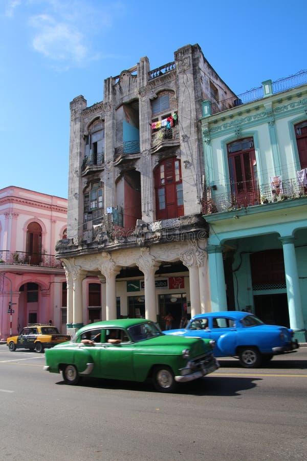 Almendrones colorido, coches viejos en una avenida grande en el La La Habana, Cuba, con los edificios coloridos fotografía de archivo