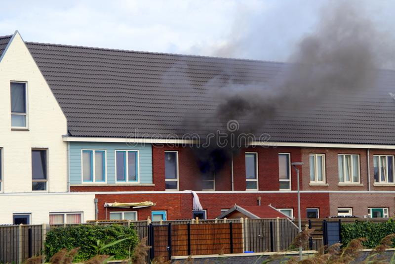 House fire. Almere Poort, The Netherlands - September 6, 2015: House fire in a resedentinal home in a Dutch suburb. Black smoke is coming out of a window royalty free stock image