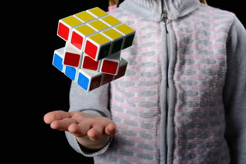 Almetyevsk City, Russia - February 7, 2017: a little girl holding a Rubik`s Cube. On a black background stock image