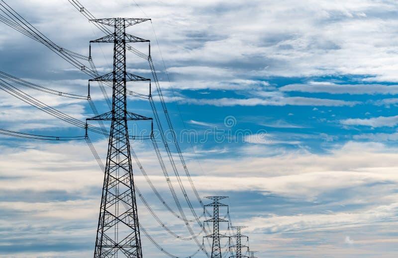 Almidón eléctrico de alta tensión y alambre eléctrico con nubes azules y blancas Polo de electricidad alto Concepto de energía y  imagen de archivo libre de regalías