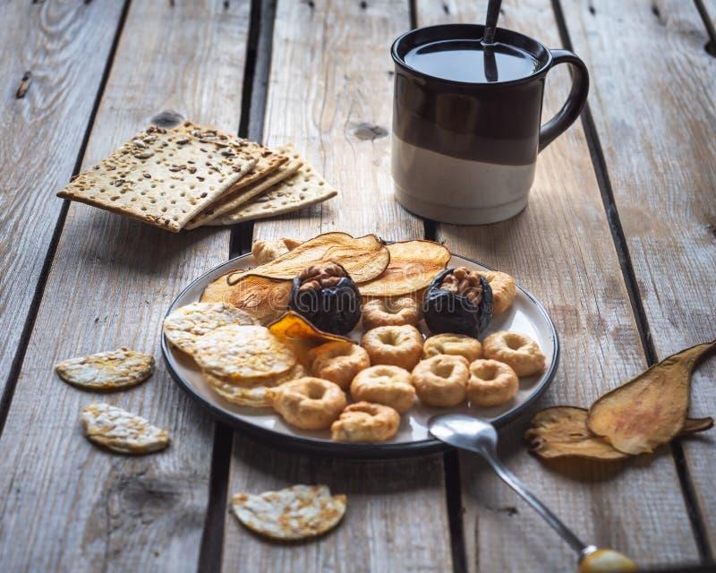 Almoço claro com chá nas cookies cerâmicas e da grão, frutos secados em uma placa redonda pequena em uma tabela rústica de madeir fotos de stock royalty free