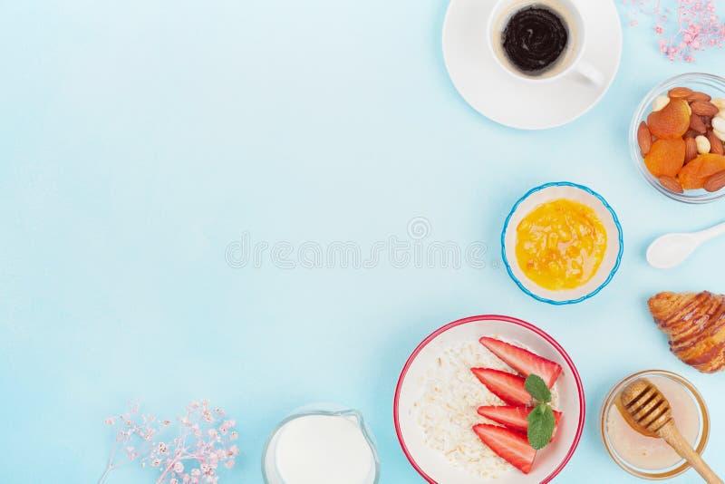 Almoço completo com café, croissant, farinha de aveia, doce, mel e fruto na opinião de tampo da mesa azul Espaço vazio para o tex fotos de stock royalty free
