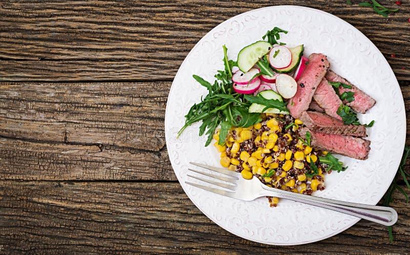 Almoço da bacia com bife e quinoa grelhado, milho, pepino, rabanete e rúcula fotografia de stock