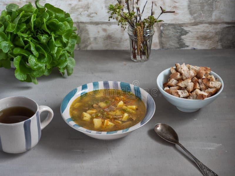 Almoço da sopa de ervilha com biscoitos, um arbusto da alface verde no fundo imagens de stock