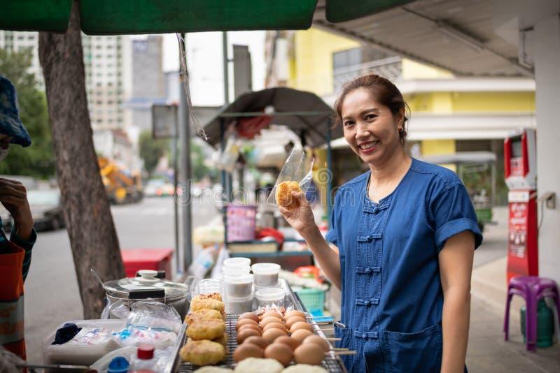 Almoço de compra da mulher asiática de um carro de vendedor de alimento da rua no bairro chinês em Banguecoque, Tailândia foto de stock
