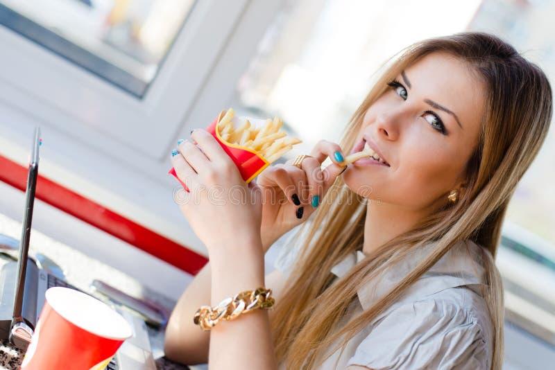 Almoço de funcionamento: a imagem de beber & de comer frita a menina loura da senhora nova bonita do negócio que tem o divertimen fotos de stock royalty free