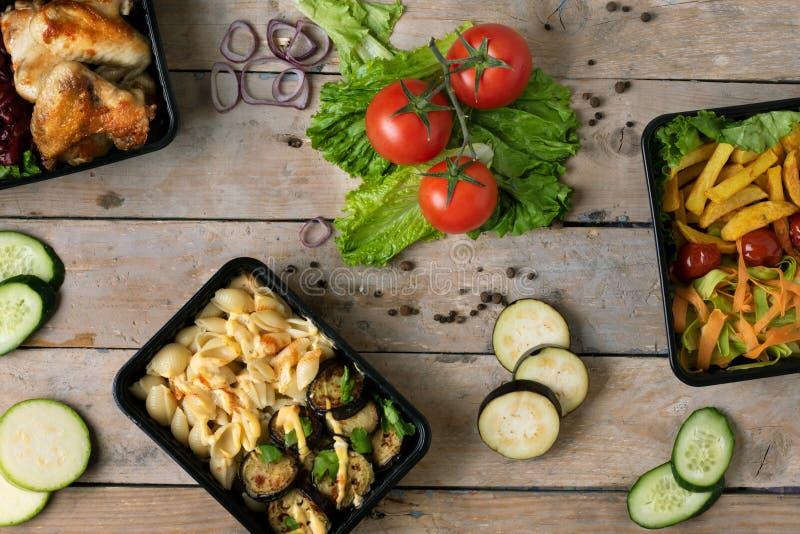 Almoço de negócio em umas caixas do alimento, asas de frango assado, vegetais cozinhados, carne cozido, refeição pronta a comer imagem de stock royalty free