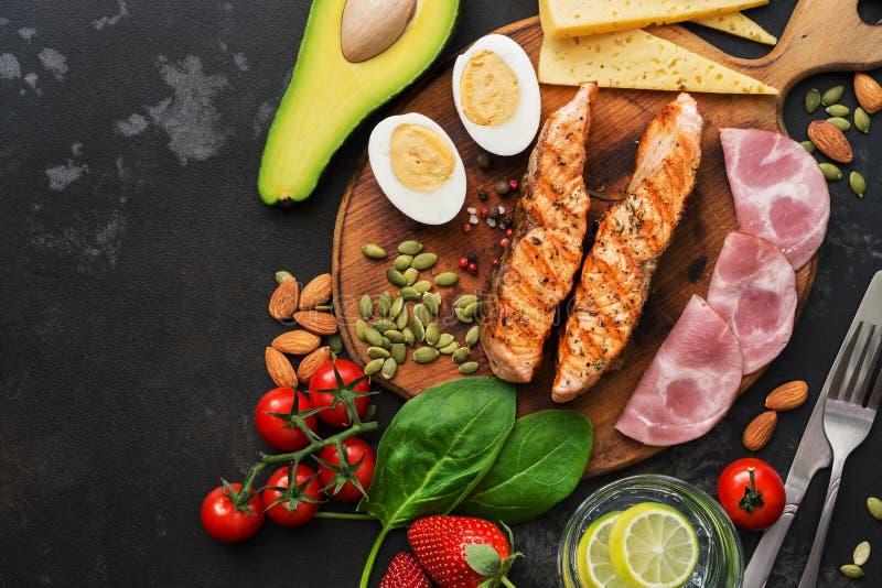 Almoço do Keto ou jantar - salmão grelhado, vegetais, ovo cozido, água com cal, porcas, presunto e queijo em um fundo escuro fotografia de stock