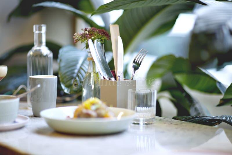 Almoço do serviço no restaurante ou no café Bebidas, água, café os houseplants aproximam a janela imagem de stock