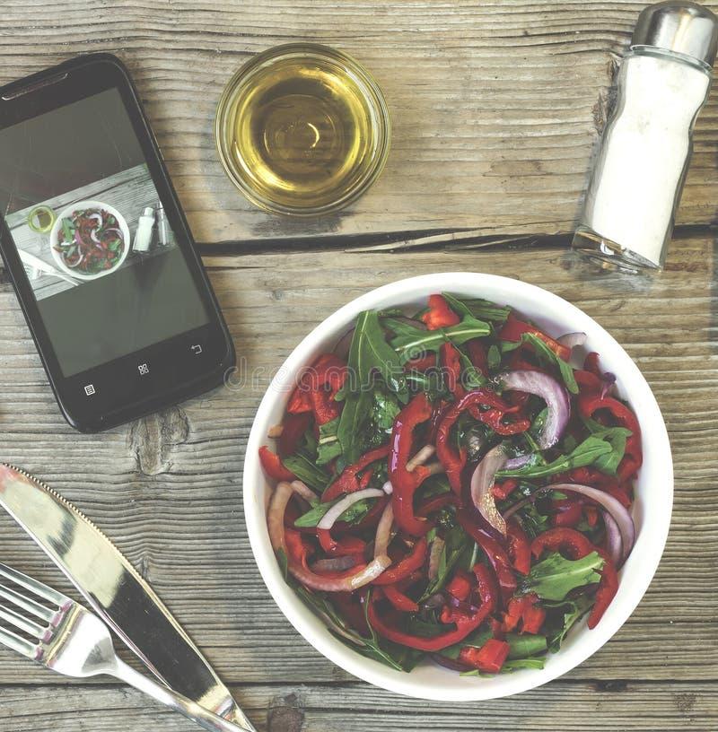 Almoço do vegetariano Salada de legumes frescos, de verdes e de pimentas doces vermelhas com azeite Na tela do smartphone, um dis foto de stock