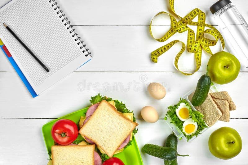 Almoço saudável no escritório no local de trabalho ou na casa sanduíche da Inteiro-grão com presunto e legumes frescos e garrafa  foto de stock