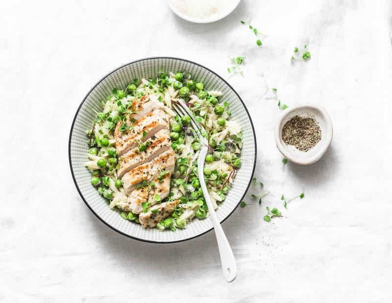 Almoço saudável - orzo, ervilhas verdes, risoto das ervas da mola e peito de frango grelhado em um fundo claro, vista superior foto de stock royalty free