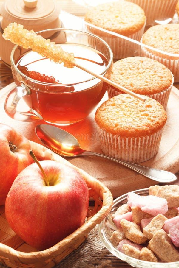 Almoce com o chá, as maçãs e os queques marrons imagens de stock royalty free