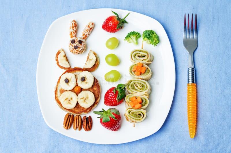 Almoce para crianças com o alimento sob a forma das caras engraçadas imagens de stock royalty free