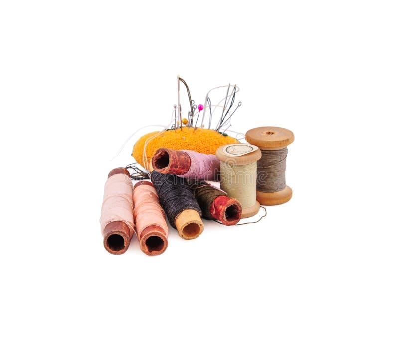Almofada de alfinetes alaranjada com agulhas e pinos e diversos carretéis da linha foto de stock