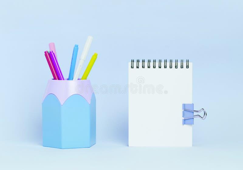 Almofada de nota e suporte vazios do lápis no fundo azul do pactel fotografia de stock