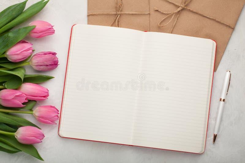 Almofada de nota vazia com pena, envelopes e as tulipas cor-de-rosa no fundo de pedra claro fotografia de stock