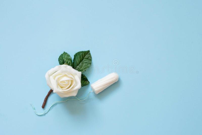 Almofadas de algod?o menstruais do tamp?o no fundo azul com flor branca Foto da concep??o da higiene da mulher Prote??o macia mac foto de stock royalty free