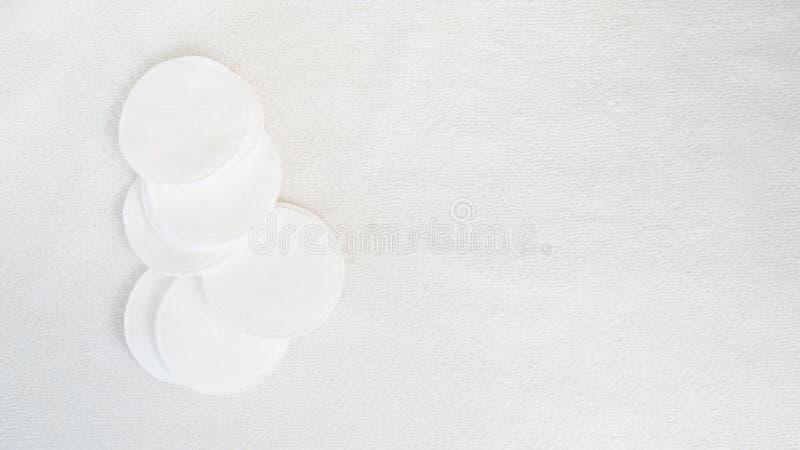 Almofadas de algodão no fundo branco de toalha com espaço da cópia Conceito do cuidado do corpo da pele imagem de stock