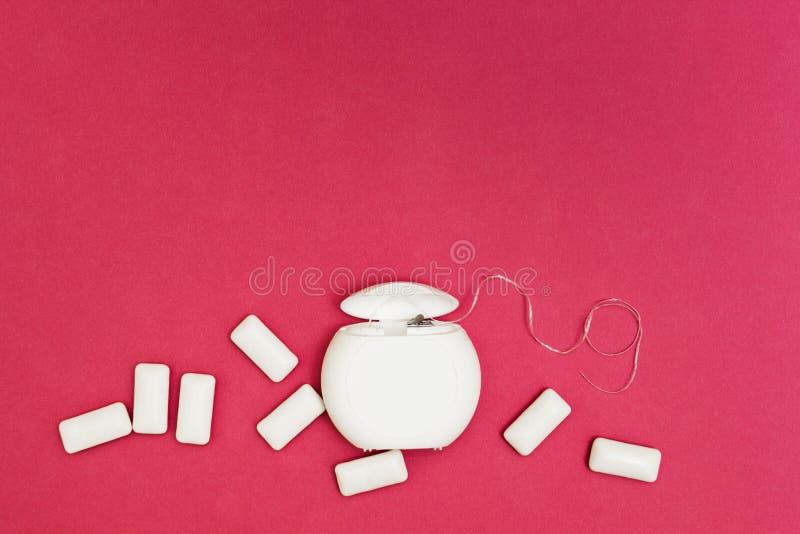 Almofadas de fio dental e de pastilha elástica em um fundo cor-de-rosa, espaço para o texto imagem de stock