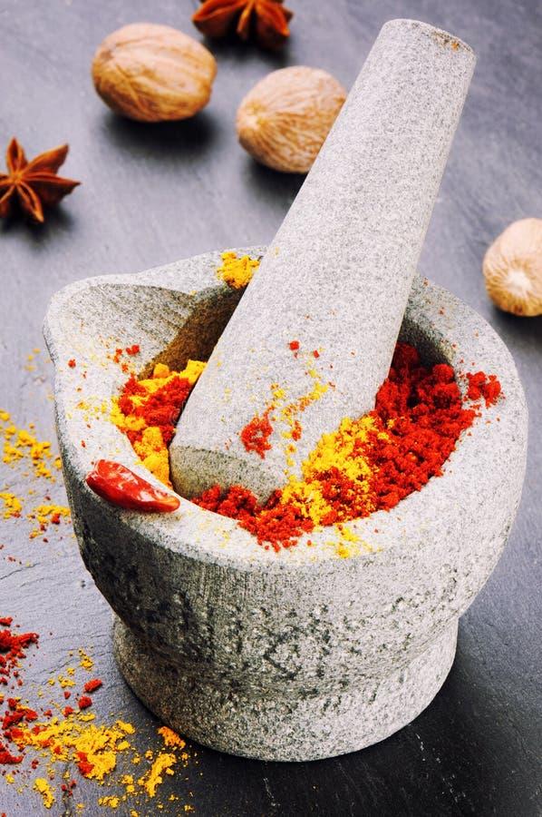 Almofariz com pimenta de pimentão e pó de caril foto de stock