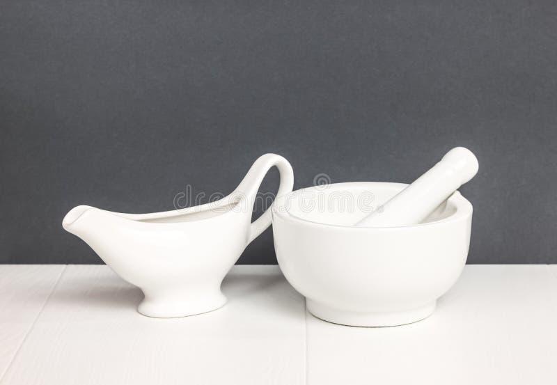 Almofariz e molho Utensílios de mesa brancos na tabela foto de stock royalty free