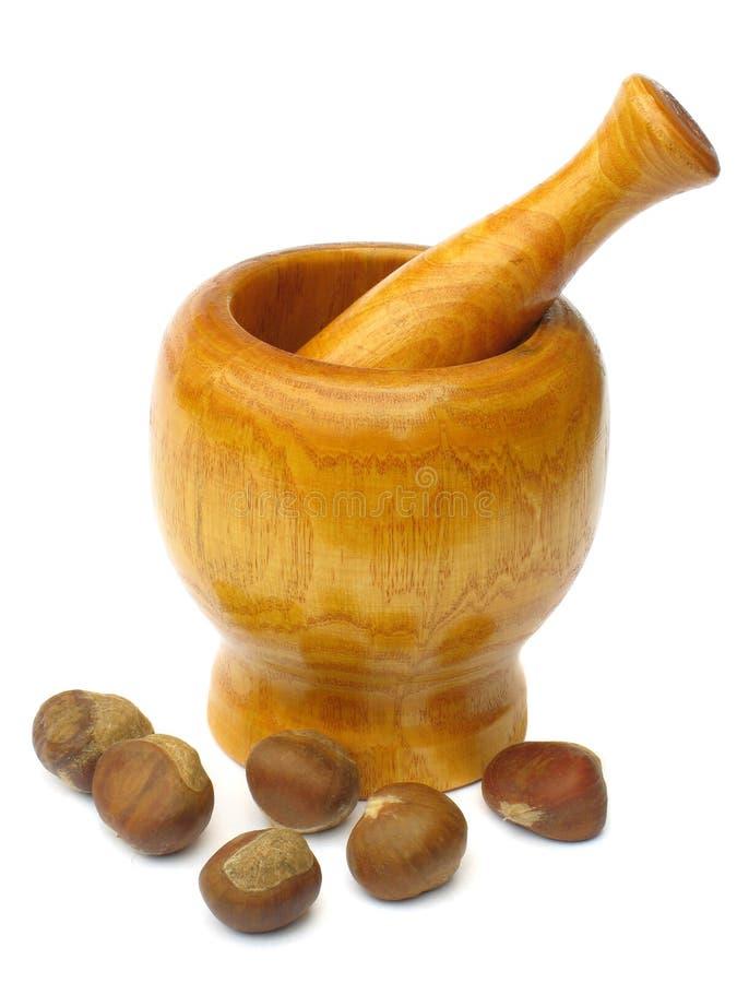 Almofariz e pilão de madeira com castanhas imagem de stock