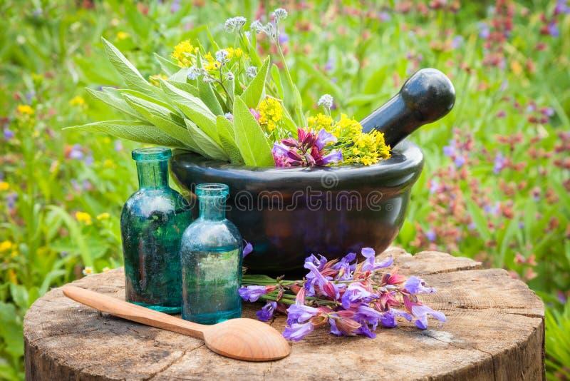 Almofariz preto com ervas curas e sábio, garrafa de vidro do óleo fotos de stock royalty free