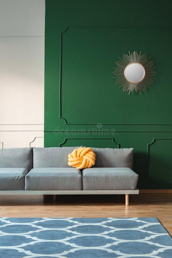 Almohada amarilla del nudo en el sofá gris largo en sala de estar gris y verde fotos de archivo libres de regalías