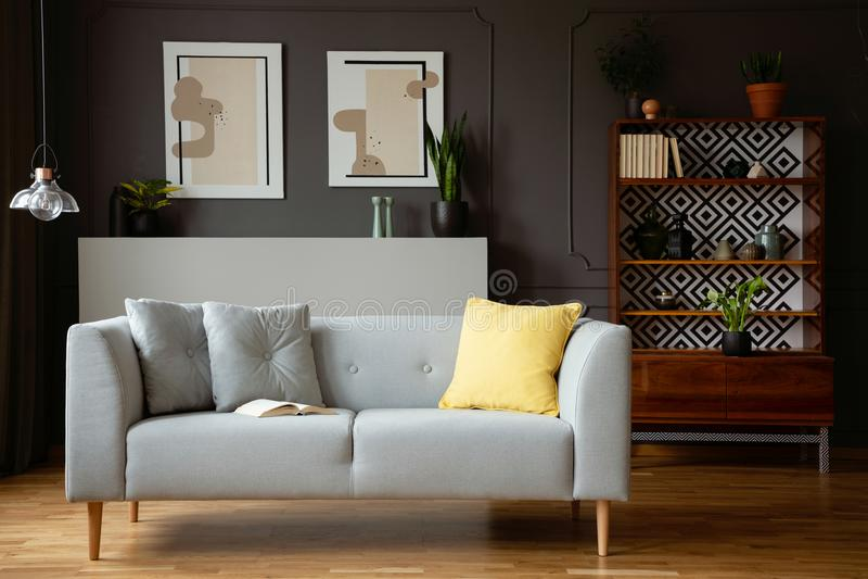 Almohada amarilla en el sofá gris en interior de la sala de estar del vintage con la lámpara y los carteles Foto verdadera fotografía de archivo