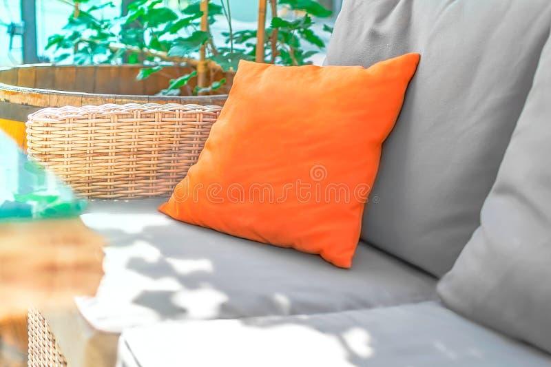 Almohada anaranjada en el sofá gris con el fondo floral de la luz del sol en terraza o el café del verano Maqueta para hacer publ fotos de archivo