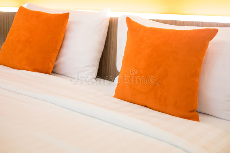 Almohada anaranjada en la decoración de la cama en interior del dormitorio imagen de archivo