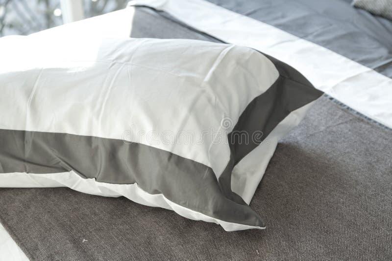 Almohada blanca y gris cómoda en cama imagen de archivo