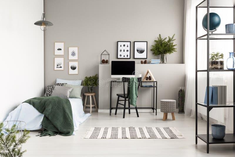 Almohada de plata, verde y modelada en lecho azul en sola cama con la manta verde en el dormitorio inspirado bosque moderno, foto imágenes de archivo libres de regalías