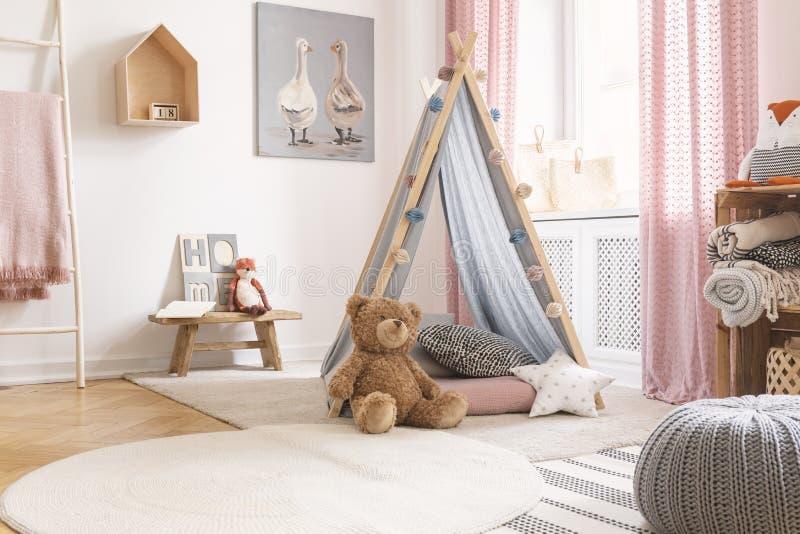 Almohada del peluche y de la estrella delante de la tienda en el interior del sitio de niño con el taburete y el cartel Foto verd imagen de archivo libre de regalías