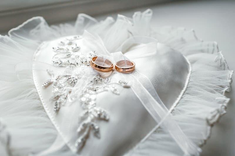 Almohada en forma de corazón con los anillos de oro de la boda del cordón imagen de archivo libre de regalías