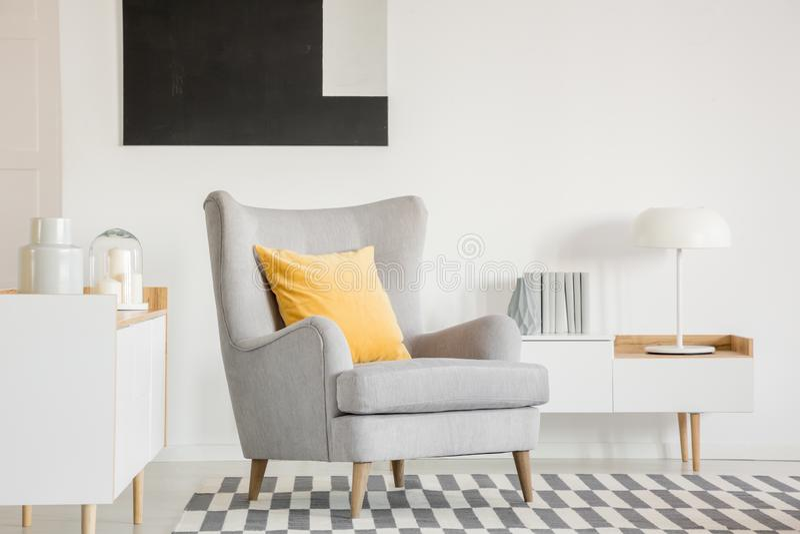 Almohada en la butaca gris en la sala de estar de moda interior con la pintura blanco y negro fotografía de archivo libre de regalías