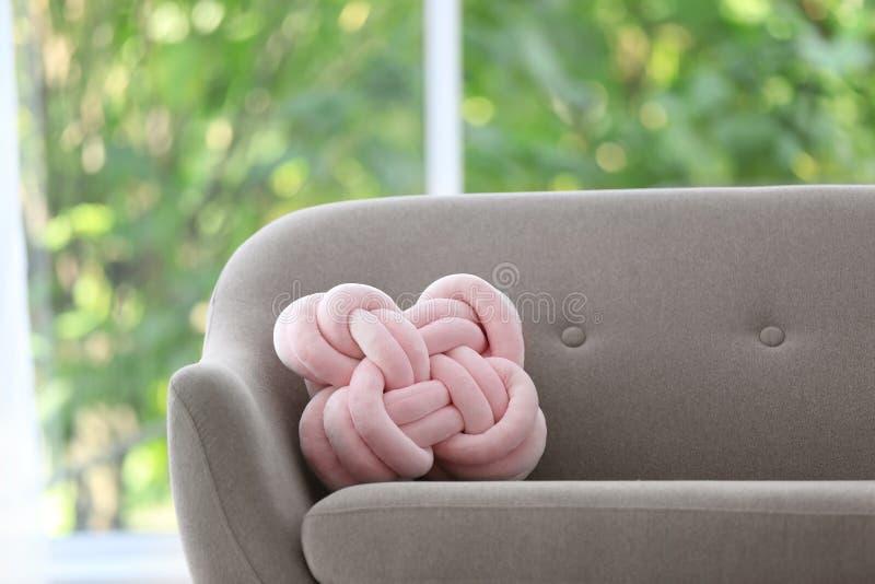 Almohada inusual en el sofá contra ventana fotografía de archivo libre de regalías