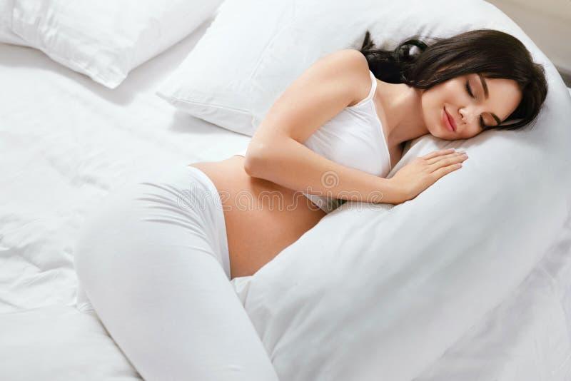 Almohada para la mujer embarazada Muchacha que duerme en la almohada del cuerpo en cama fotografía de archivo libre de regalías