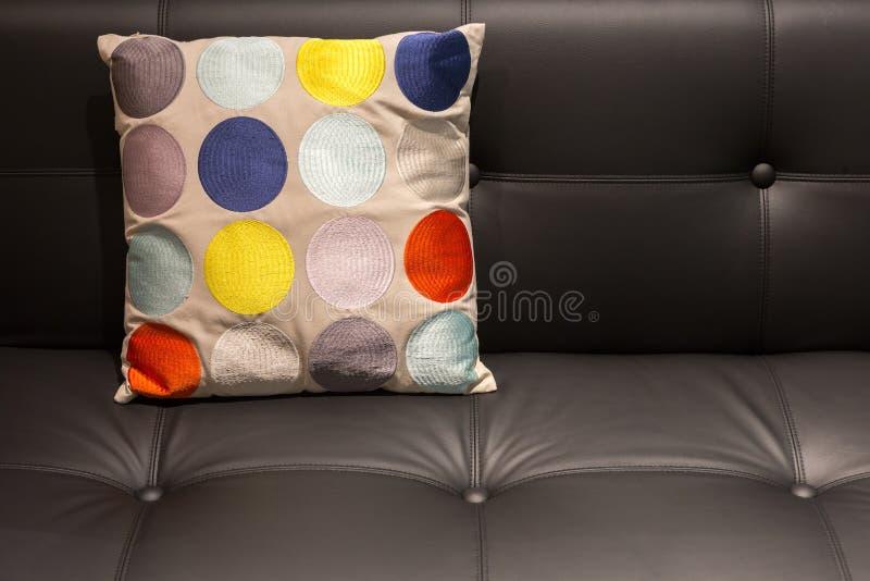 Almohada punteada colorida en un sofá de cuero negro imagen de archivo libre de regalías
