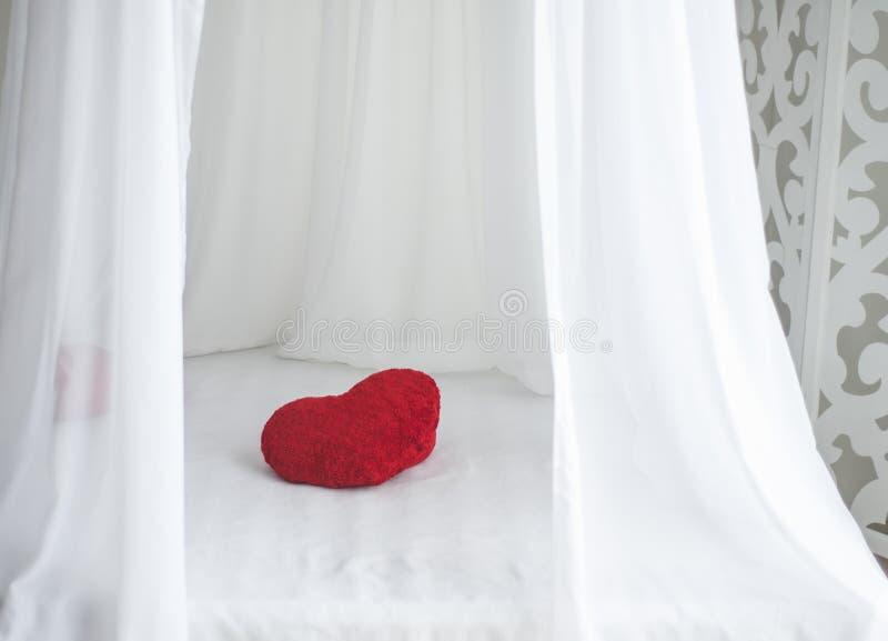 Almohada roja de la forma del corazón en la hoja de cama blanca fotos de archivo