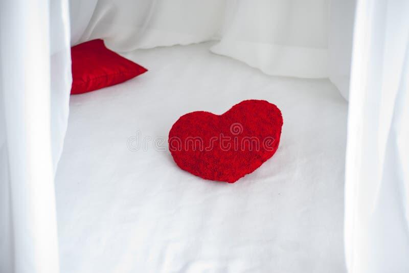 Almohada roja de la forma del corazón en la hoja de cama blanca foto de archivo