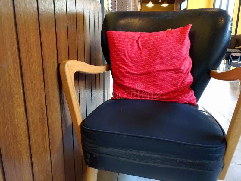 Almohada roja en la silla negra en una cafetería fotografía de archivo libre de regalías