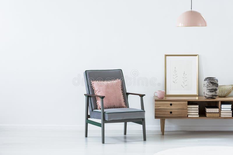Almohada rosada en la butaca azul al lado de un armario de madera en la vida foto de archivo libre de regalías