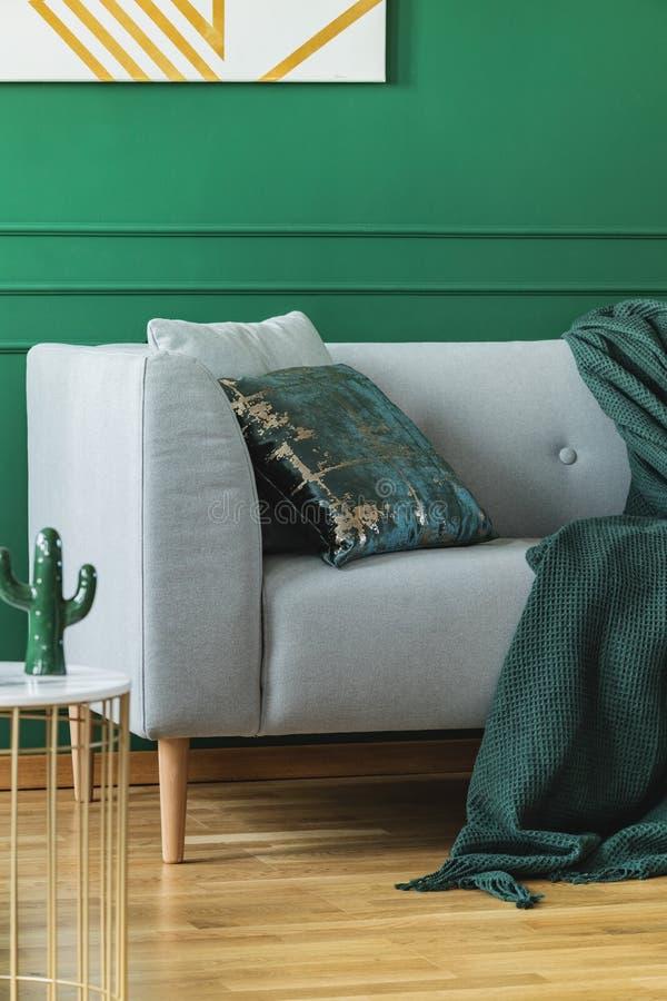 Almohada verde esmeralda y manta en el sofá escandinavo en sala de estar de moda imagenes de archivo