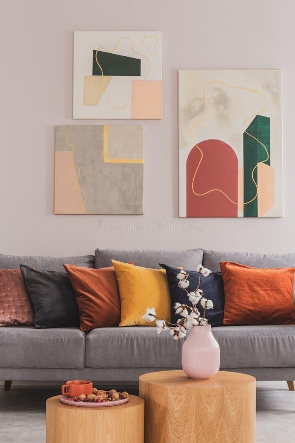 Almohadas amarillas, anaranjadas, negras y marrones en el sofá escandinavo gris cómodo en la sala de estar brillante interior con fotos de archivo libres de regalías