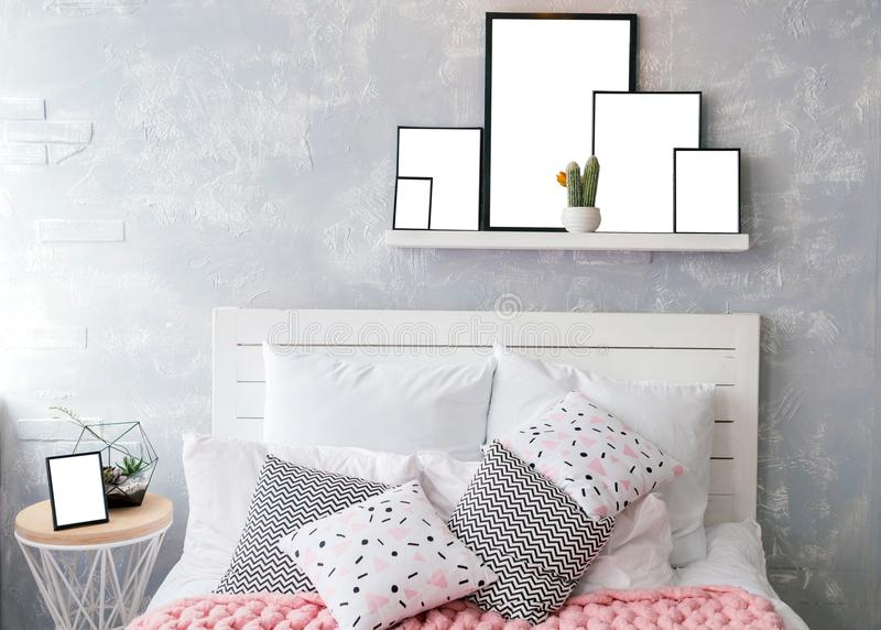Almohadas blancas y coloreadas en cama del woodenl con el cabecero blanco foto de archivo