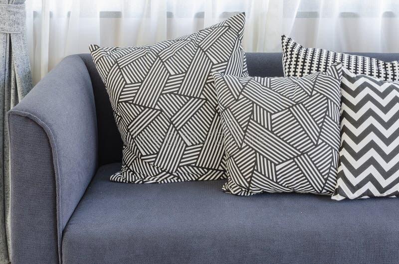 Almohadas blancos y negros en el sofá azul en sala de estar fotos de archivo libres de regalías