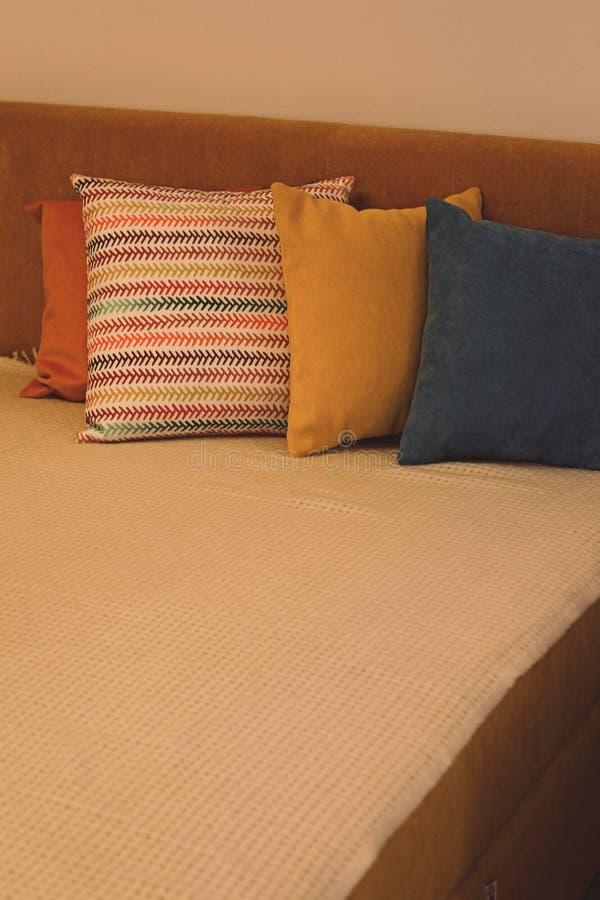 Almohadas coloreadas y con el modelo en una tira de almohadas en cama Interior del dormitorio moderno con la cama acogedora Resto fotos de archivo